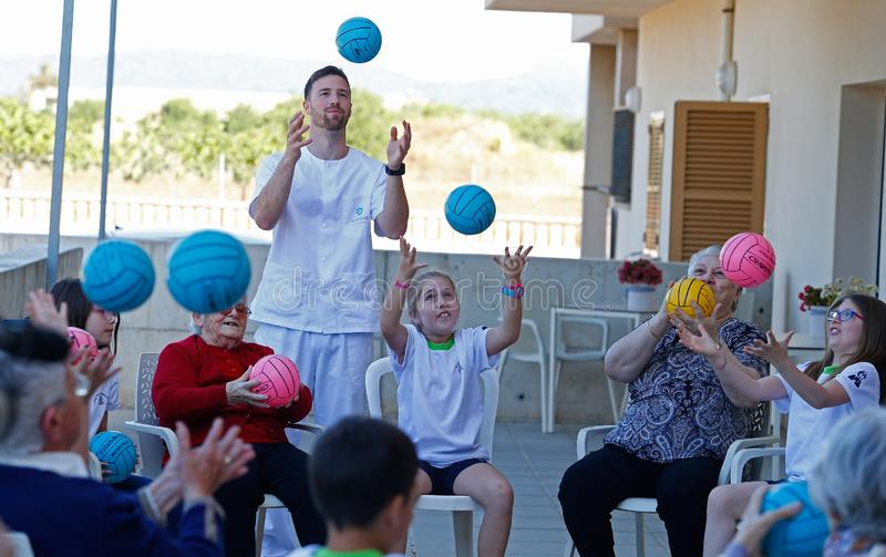 Seniors and childs during therapeutical activities on a nursing home in Mallorca. Seniors with childs and their Medical assistant practice some coordination royalty free stock photography