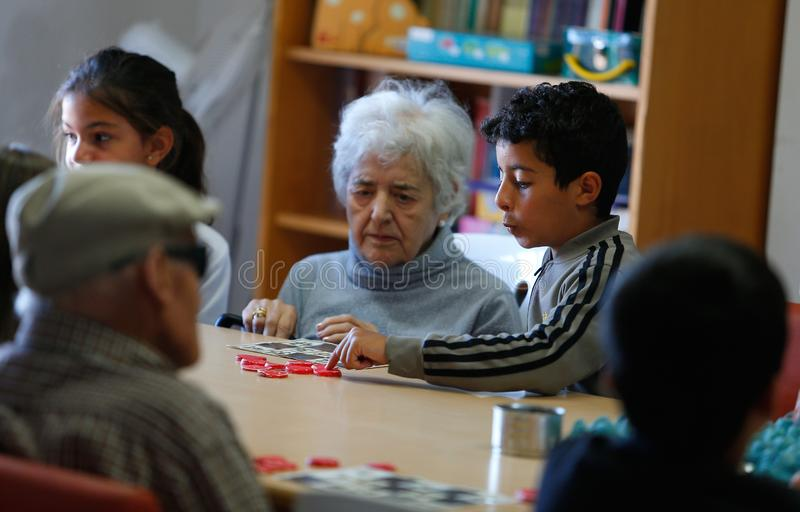 Seniors and childs during therapeutical activities on a nursing home in Mallorca. Seniors with childs and their Medical assistant practice some mind games on the royalty free stock photo