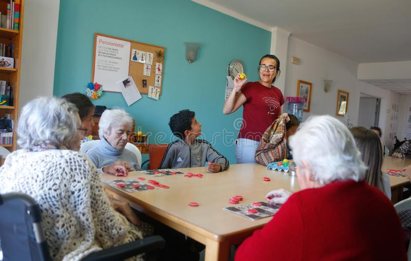 Seniors and childs during therapeutical activities on a nursing home. Seniors with childs and their Medical assistant practice some mind games on the terrace of stock photos