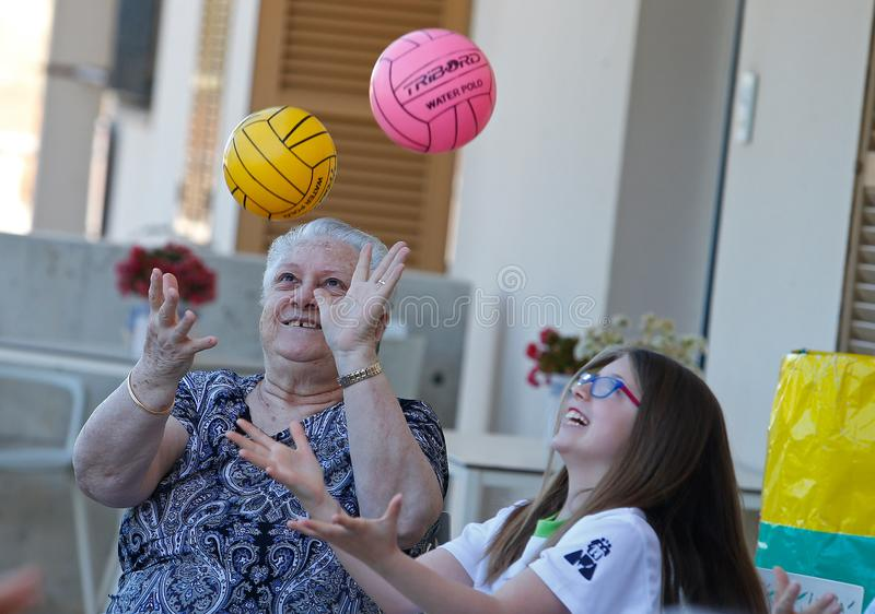 Seniors and childs during therapeutical activities on a nursing home in Mallorca. Seniors with childs practice some coordination games on the terrace of their stock photos
