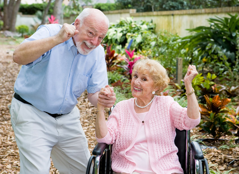 Seniors Conquering Adversity. Happy senior couple conquering the challenge of her disability together royalty free stock photography