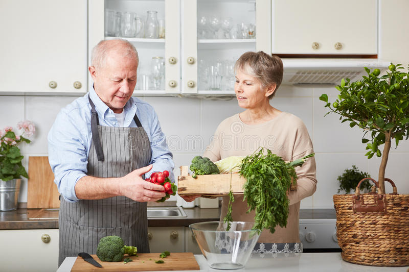 Seniors cooking for leisure healthy meal. Seniors cooking for leisure healthy vegan meal in cooperation royalty free stock image