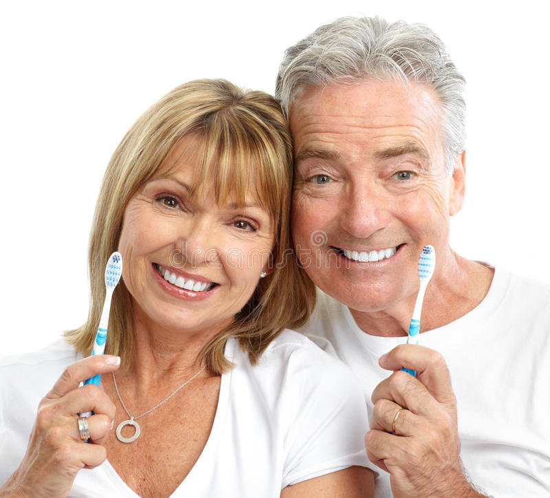 Seniors couple. Happy seniors couple with toothbrushes. Healthy teeth. Isolated over white background stock photo
