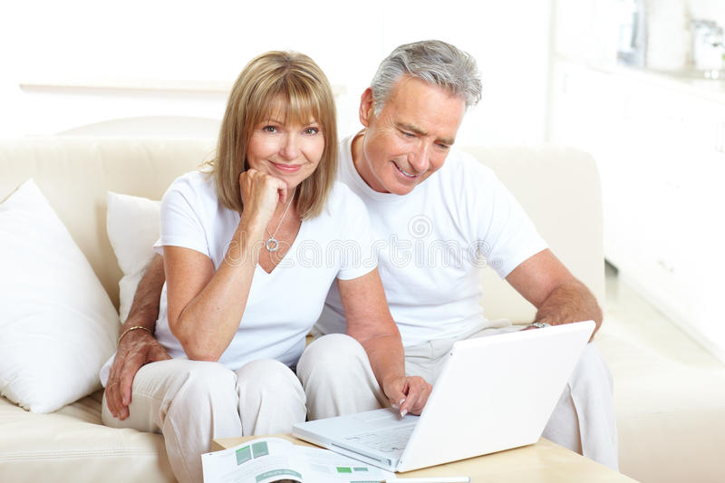 Seniors couple. Working with laptop at home royalty free stock images
