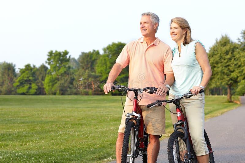 Seniors couple biking. Happy elderly seniors couple biking in park royalty free stock photography