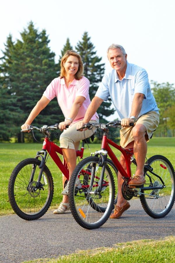 Seniors couple biking stock images