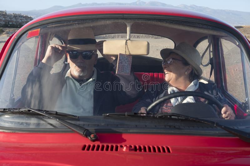 Seniors couple driving and having fun inside an old red car. Elderly couple travelling inside a red car, having fun laughing with two hats. Vacation time and royalty free stock image
