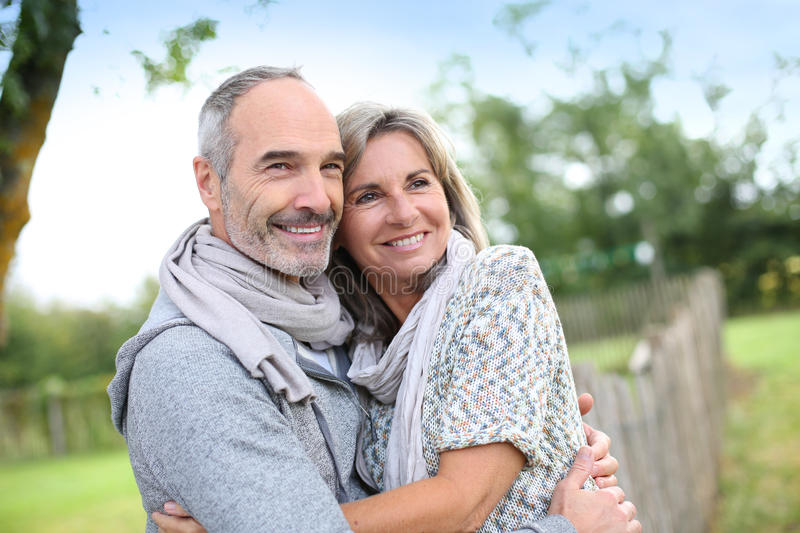 Seniors couple embracing each other in fields. Cheerful senior couple enjoying peaceful nature royalty free stock photos