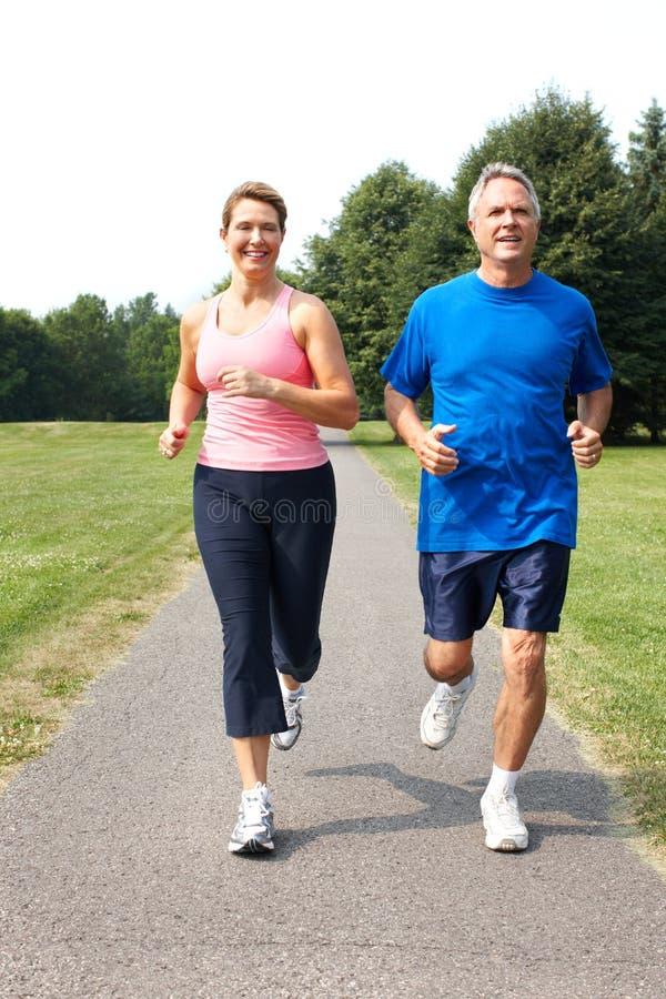 Seniors couple jogging. Happy elderly seniors couple jogging in park stock images