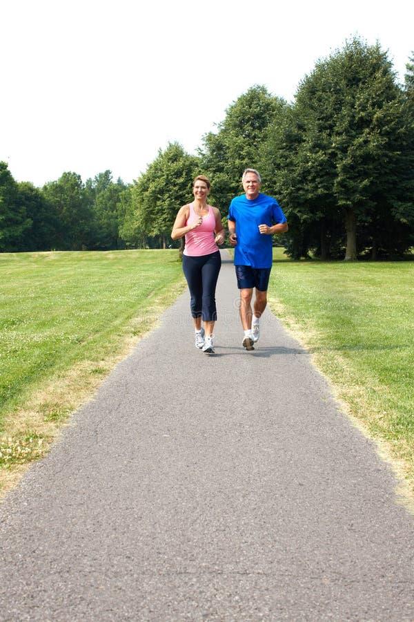 Seniors couple jogging. Happy elderly seniors couple jogging in park stock photos