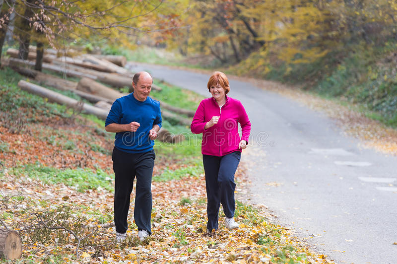 Seniors couple jogging. Senior Couple doing sport outdoors stock photography