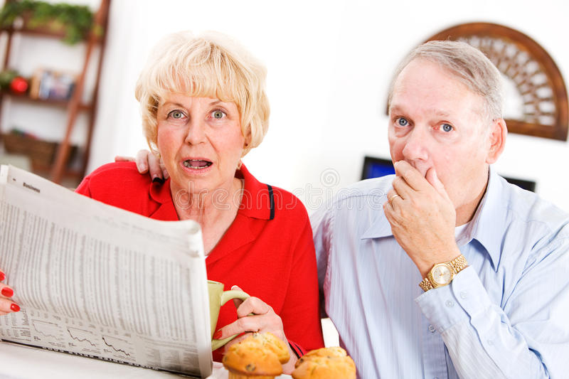 Seniors: Couple Shocked By Something In Newspaper. Series with a senior couple in their 60s, at home and , with various props and themes stock photo