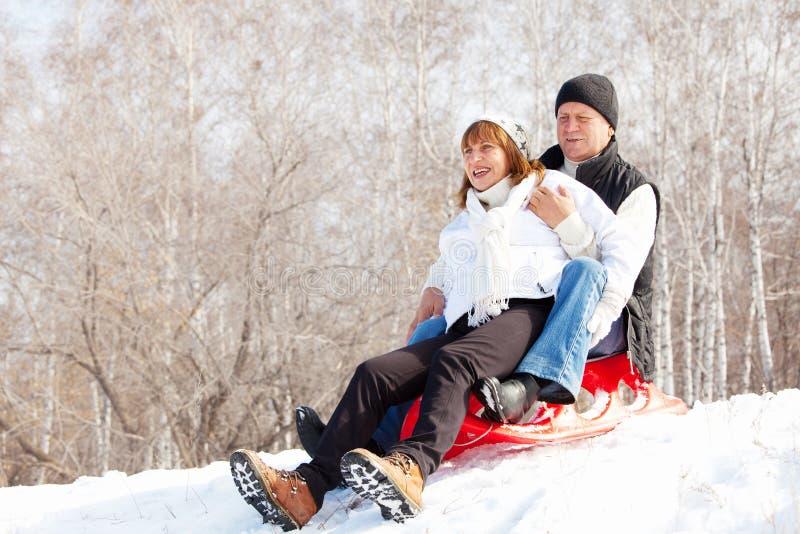Seniors couple sledding. Mature couple sledding. Seniors couple on sled in winter park royalty free stock photography