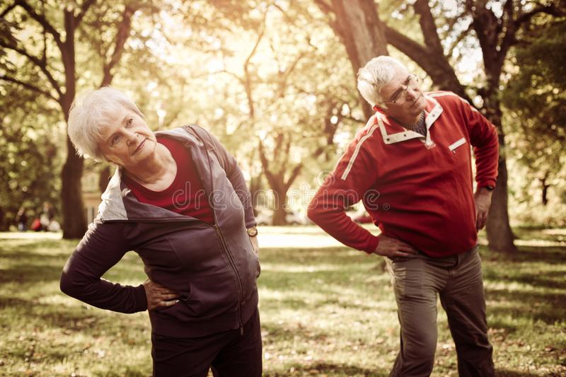 Seniors couple in sports clothing working stretching and. Active seniors couple in sports clothing working stretching and exercise in park stock images