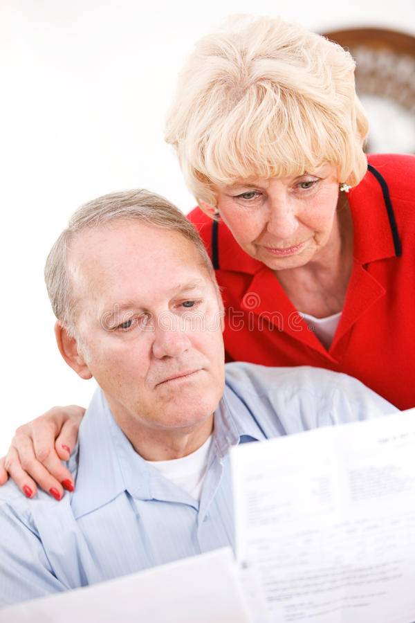Seniors: Couple Upset At Amount Of Bills. Series with a senior couple in their 60s, at home and , with various props and themes stock photography
