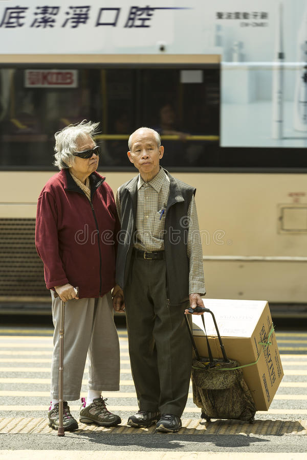 Seniors couple. On the way from the market wait to cross the street in down town Hong Kong royalty free stock photography