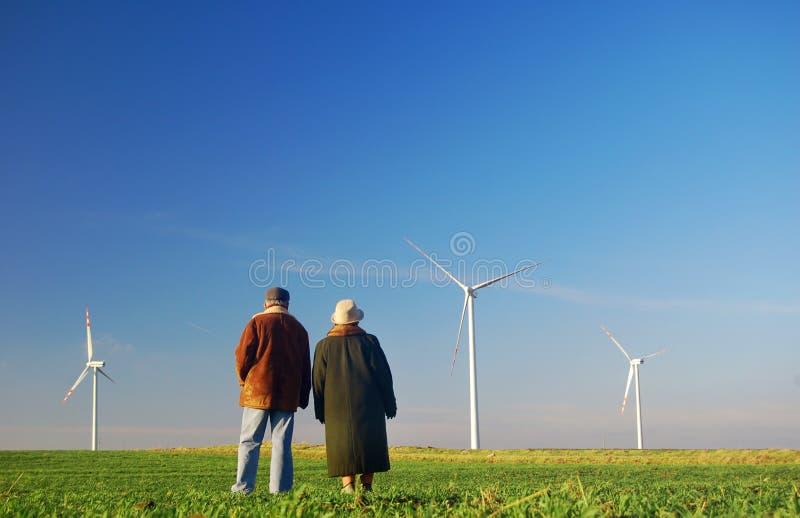 Seniors' couple and wind turbines. Seniors' couple looking on wind turbines stock photography