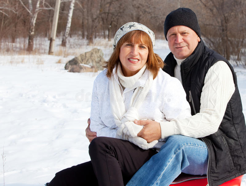 Seniors couple in winter park. Happy seniors couple in winter park. Elderly mature people royalty free stock photo