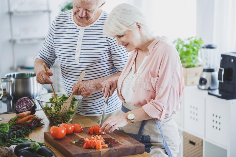 Seniors on culinary workshop. Lovely seniors on culinary workshop cutting tomatoes on cutting board and making a salad with eggplant, cabbage, carrot and garlic royalty free stock photo