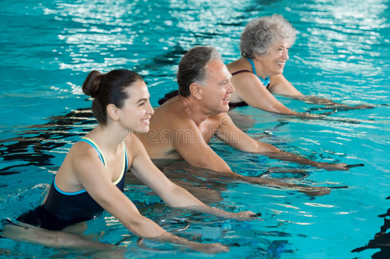 Seniors cycling on aqua bike. Happy smiling mature men and old women cycling on a swimming bike in swimming pool. Happy and healthy senior people enjoying royalty free stock image