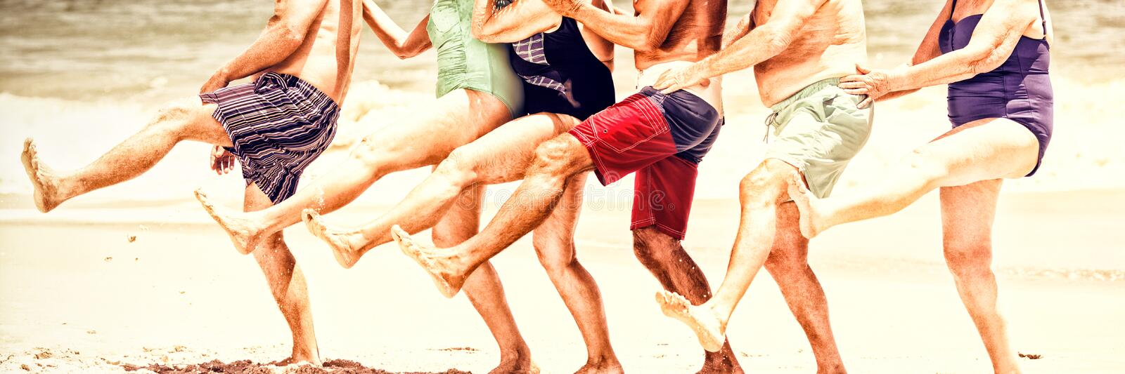 Seniors dancing in a row at the beach royalty free stock images