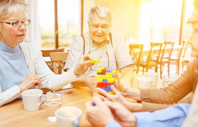 Seniors with dementia and Alzheimer play. Seniors with dementia and Alzheimer`s play together with building blocks in the nursing home royalty free stock photo