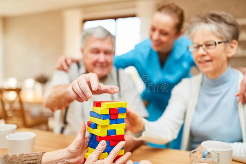Seniors with dementia play with building blocks stock images