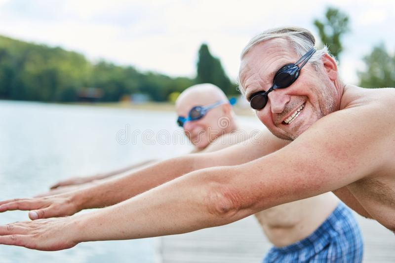 Seniors with diving goggles go swimming. Two seniors with diving goggles go swimming and doing gymnastics stock photo