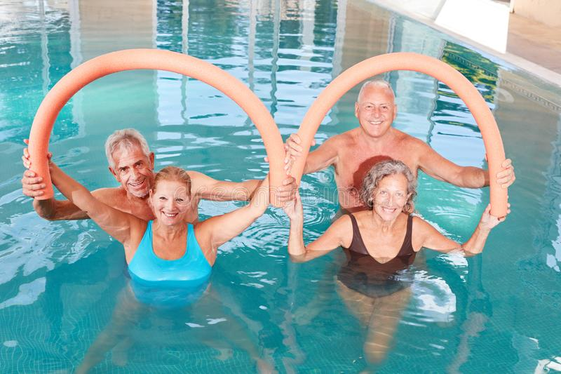 Seniors do exercises with swimming noodle. In the aqua gym course royalty free stock photo