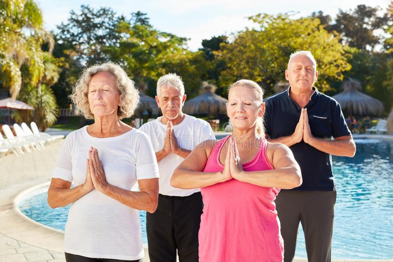 Seniors do a yoga exercise by the pool stock images