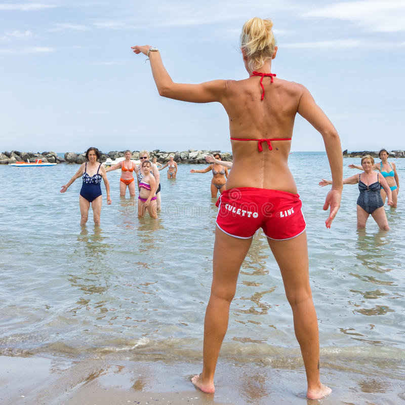Seniors doing fitness on Cattoica beach, Emilia Romagna, Italy. CATTOLICA, ITALY - JUNE 23: aquagym on the beach on June 23, 2014 in Cattolica, Emilia Romagna royalty free stock image