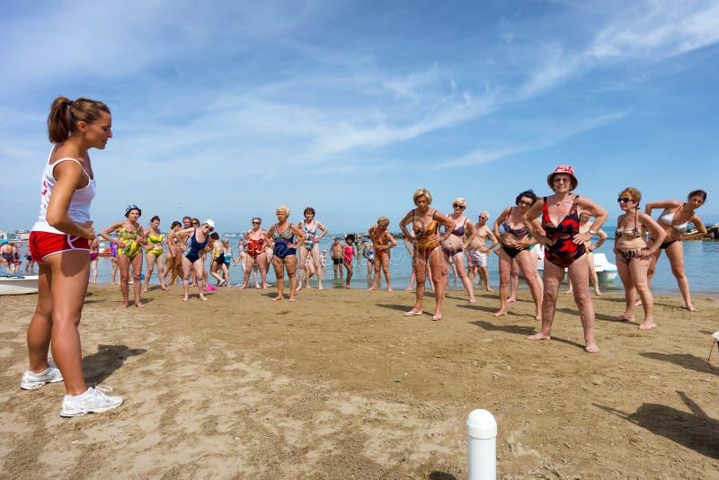 Seniors doing fitness on Cattoica beach, Emilia Romagna, Italy. CATTOLICA, ITALY - JUNE 23: fitness on the beach on June 23, 2014 in Cattolica, Emilia Romagna royalty free stock photos