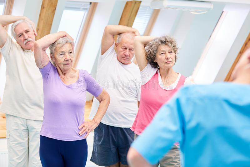 Seniors doing a healthy stretching exercise. Senior group doing a healthy stretching exercise in back exercises royalty free stock photos