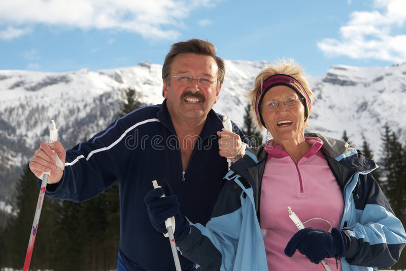 Seniors doing sports. A senior couple outdoor in a winter setting. The active couple is about to go crosscountry skiing royalty free stock image