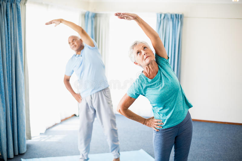 Seniors doing stretching. In a studio stock photos
