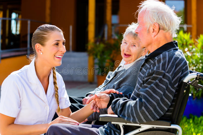 Seniors eating candy in garden of nursing home. Seniors, couple of men and women sitting in wheelchair, nurse holding hands with them royalty free stock image