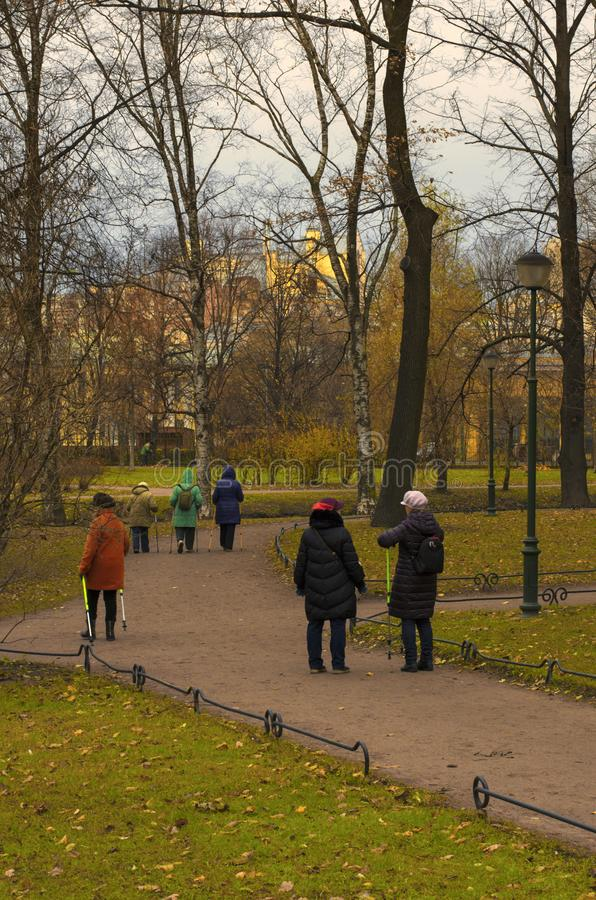 Seniors engaged in Nordic walking in the Park in late autumn. Saint Petersburg, Russia - November 16, 2018: Seniors engaged in Nordic walking in the Park on a stock image