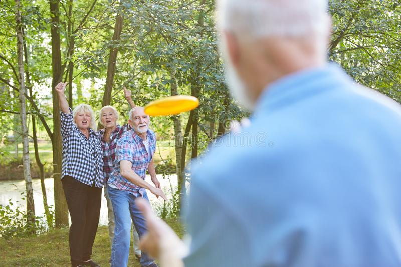 Seniors enjoy the Frisbee game. Seniors enjoy playing Frisbee game in summer on vacation in the garden royalty free stock image
