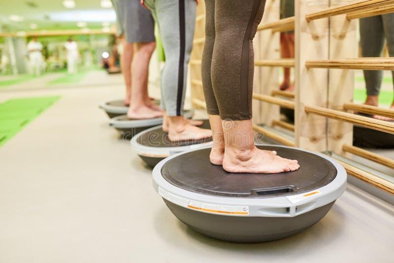 Seniors exercise balance on the Bosu Ball stock image