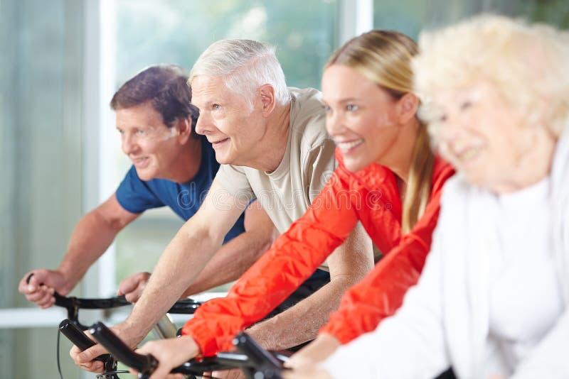 Seniors exercise while spinning stock photos