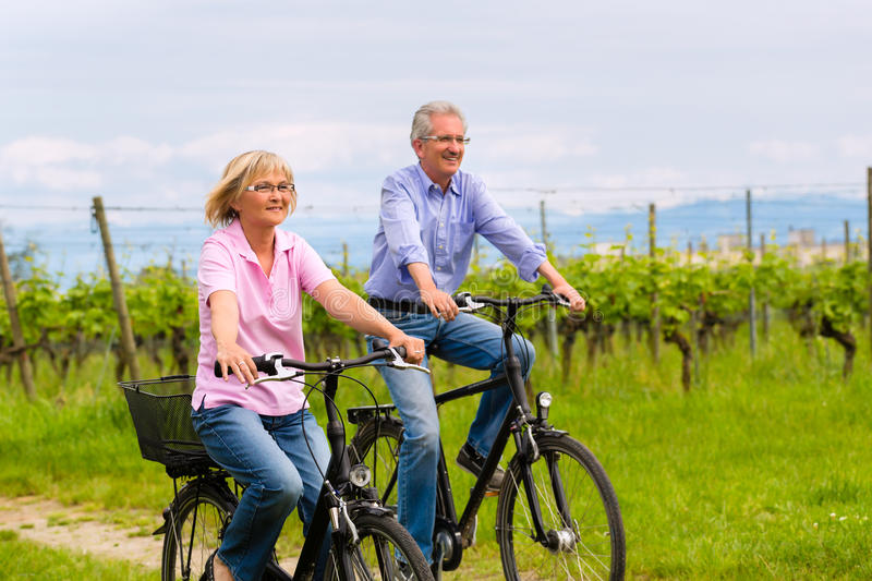 Seniors exercising with bicycle stock photography