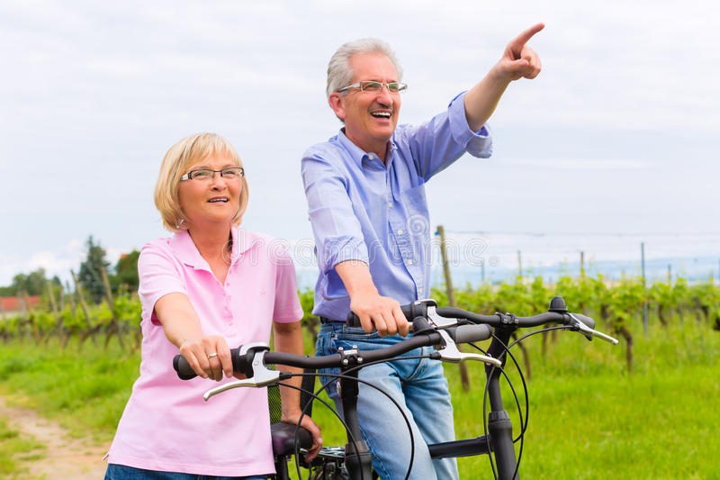Seniors exercising with bicycle stock image