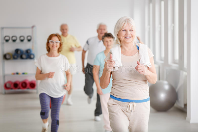 Seniors exercising together. Happy active seniors exercising together in white spacious room royalty free stock images