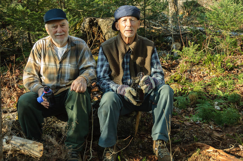 Seniors at Fall hunter time. Elderly seniors hunters resting and taking a drink after working in the woods of Quebec, Canada royalty free stock photography