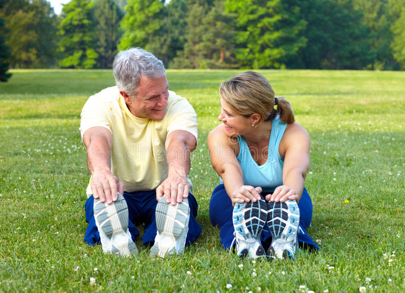 Seniors fitness. Happy elderly seniors couple working out in park stock photos