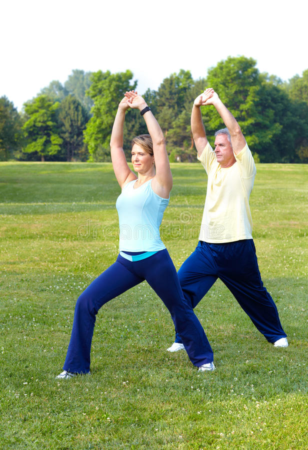 Seniors fitness. Happy elderly seniors couple working out in park royalty free stock photo