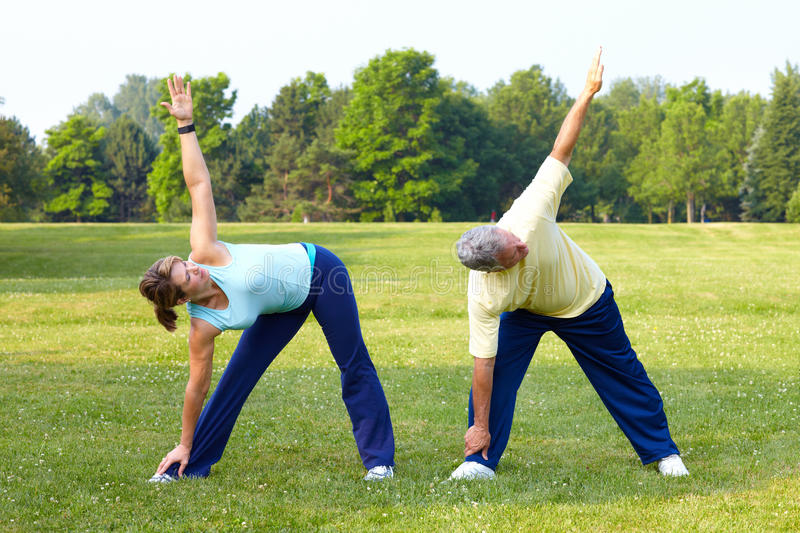 Seniors fitness. Happy elderly seniors couple working out in park royalty free stock images