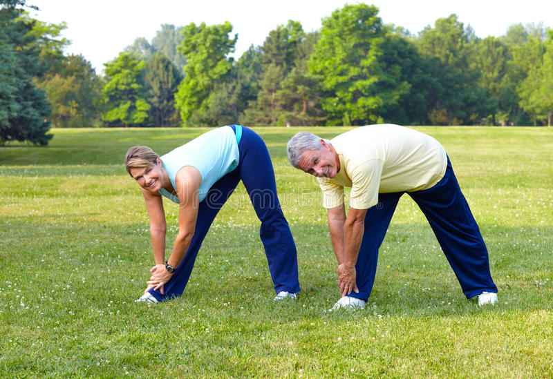 Seniors fitness. Happy elderly seniors couple working out in park stock photo