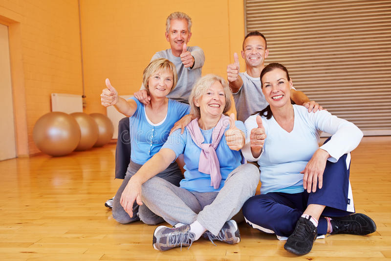 Seniors in fitness center holding stock photography