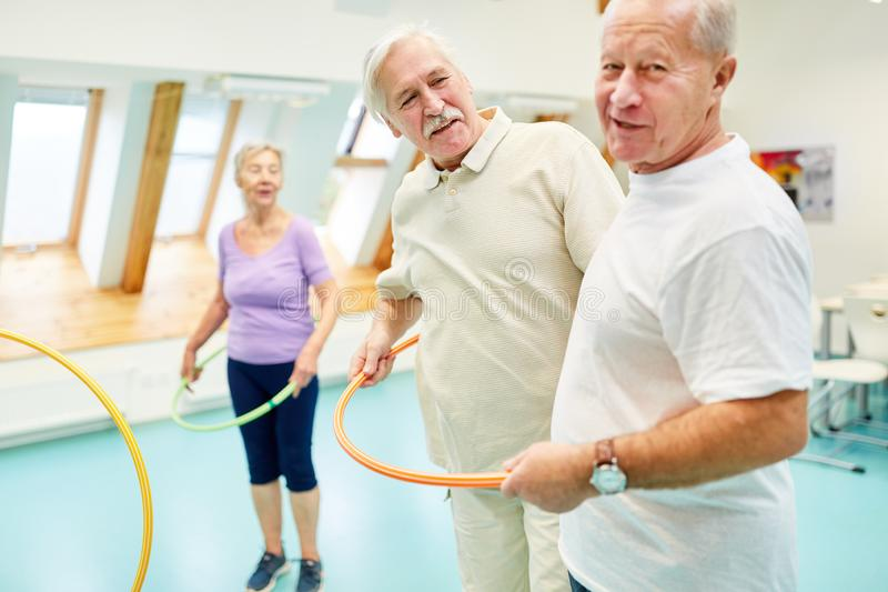 Seniors in the fitness center with tires. Seniors doing rehab sport with tires work out together in the fitness center stock photos